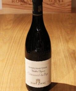Bouteille de Châteauneuf du Pape Vieilles Vignes Alain Jaume sur une table en bois
