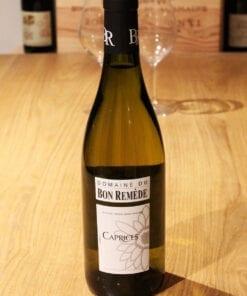 bouteille Caprices Domaine Bon Remede sur table en bois